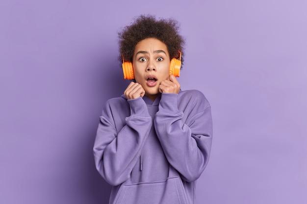 Mulher de cabelo encaracolado assustada encara com expressão omg reage a algo horrível usa fones de ouvido estéreo para ouvir música vestida com um moletom casual.