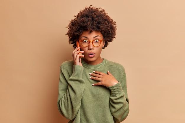 Mulher de cabelo encaracolado atônita fala ao telefone descobre que acontecimento terrível aconteceu segura smartphone perto de suportes para orelha com respiração suspensa usa óculos transparentes e suéter isolado sobre parede bege