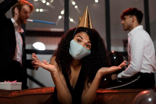 Mulher de cabelo encaracolado com máscara médica na festa de ano novo
