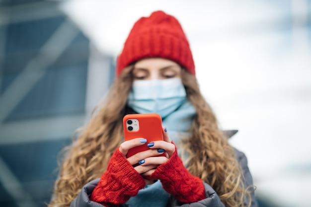 Mulher de cabelo encaracolado com máscara médica protetora desce para a rua usando mensagens de texto por telefone, rola surfa