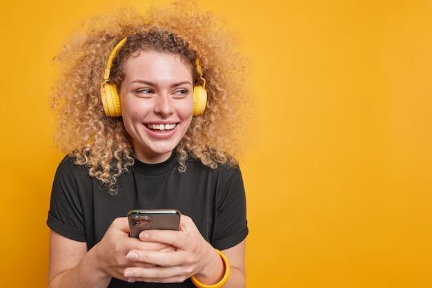 Mulher de cabelo encaracolado feliz desvia o olhar com alegria segura o smartphone para verificar o feed de notícias tem expressão alegre ouve música através de fones de ouvido usa camiseta preta isolada sobre a parede amarela