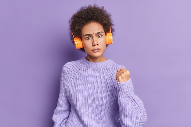 Mulher de cabelo encaracolado irritada mostra o punho, expressa raiva, ouve música com fones de ouvido sem fio