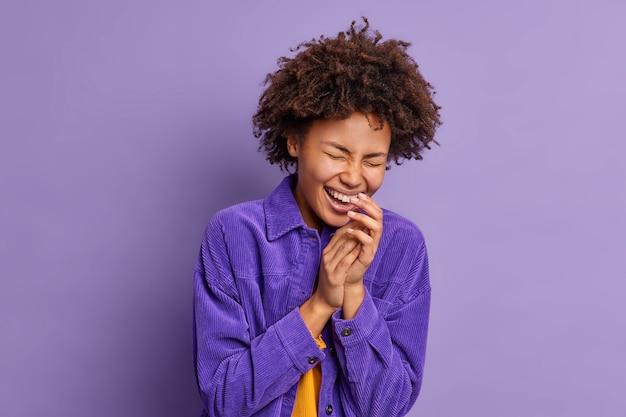 Mulher de cabelo encaracolado muito feliz que mantém as mãos juntas, ri de emoções positivas vestida com roupas elegantes e sorri amplamente