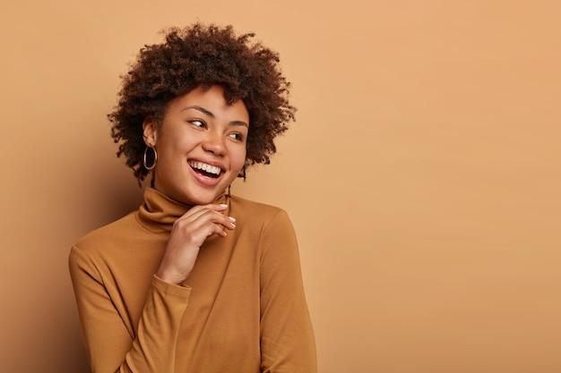 Mulher de cabelo encaracolado olha alegremente para o lado, toca o queixo suavemente, tem um largo sorriso dentu