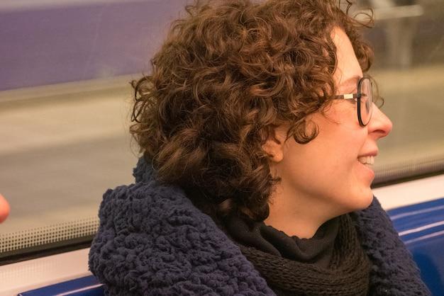 Mulher de cabelo encaracolado posando no metro.