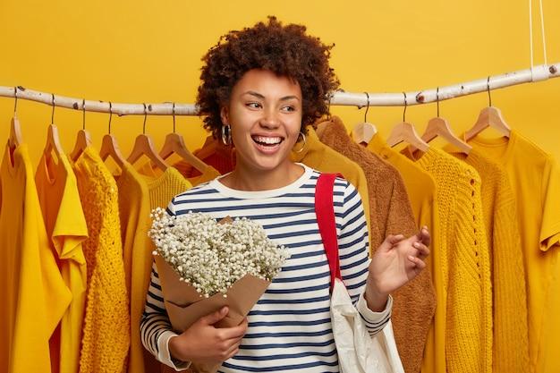 Mulher de cabelo encaracolado positiva em um suéter listrado, carrinhos com buquê e sacola de compras, retorna da loja