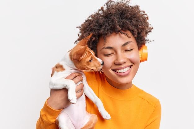 Mulher de cabelo encaracolado positiva sente-se cuidada e responsável segurando um pequeno cão de raça junto em casa ouve música em fones de ouvido sem fio fecha os olhos com ternura isolada sobre a parede branca