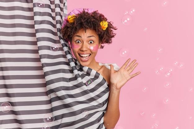 Mulher de cabelo encaracolado refrescado positivamente levanta a palma da mão se sente muito feliz e animada toma banho aplica adesivos de colágeno gosta de cuidar da pele e procedimentos de higiene se diverte no banheiro