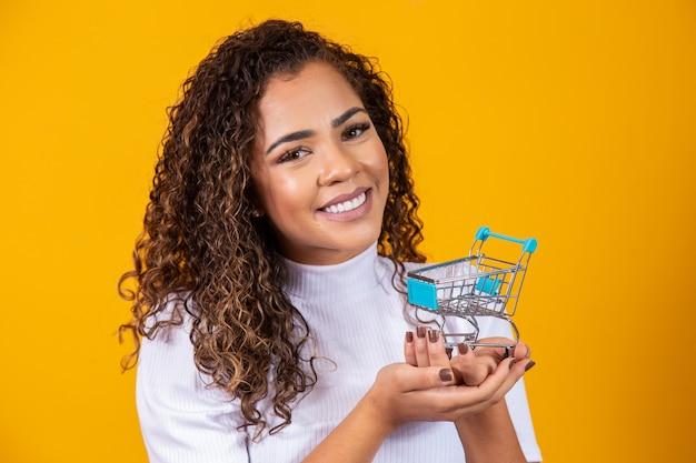 Mulher de cabelo encaracolado sorridente no conceito de compras. mulher jovem com um carrinho em miniatura. comércio eletrônico e negócios. carro de compras. mulher compradora. fundo amarelo.