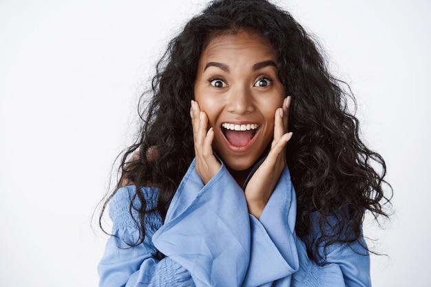 Mulher de cabelo encaracolado surpresa e feliz, entusiasmada, em uma blusa azul elegante, boca aberta, queixo caído de espanto, grita de felicidade, reage a notícias maravilhosas e surpreendentes, parede branca