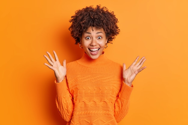 Mulher de cabelo encaracolado surpresa e feliz levanta as palmas das mãos e olha maravilhada com os sorrisos da câmera e usa um suéter casual isolado sobre uma parede laranja
