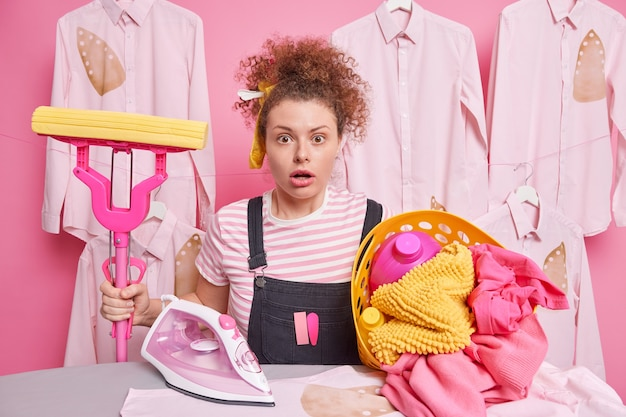 Mulher de cabelo encaracolado surpresa faz trabalho doméstico segura poses de esfregão perto de tábua de passar roupas com cesto de roupa suja chocada por ter tanto trabalho sobre a casa vestida com roupas casuais. conceito de limpeza