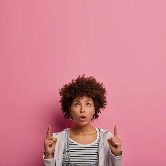 Mulher de cabelo encaracolado surpresa fica envergonhada, aponta o dedo indicador para cima, mostra uma promo incrível, vestida casualmente, conta sobre um evento legal acontecendo lá em cima, abre a boca de espanto