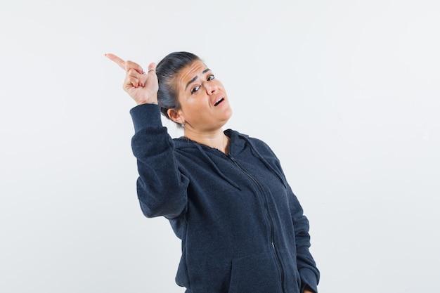 Mulher de cabelo escuro apontando para trás com jaqueta e parecendo descontente