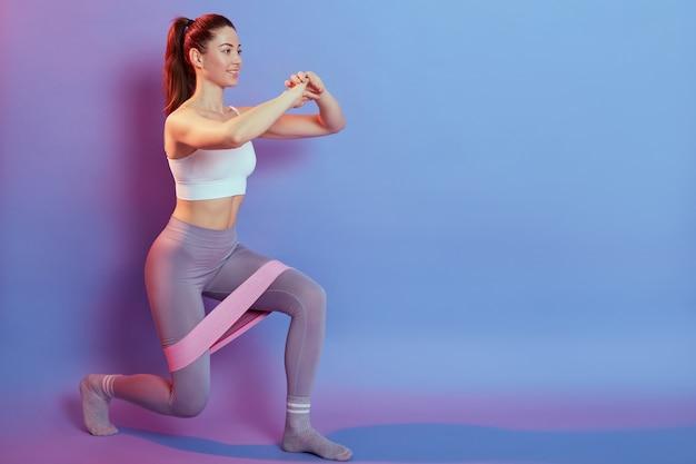 Mulher de cabelo escuro com rabo de cavalo em leggins e top esportivos, estocadas com elástico de fitness esportivo isolado
