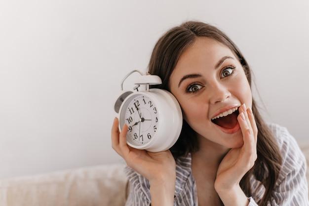 Mulher de cabelo escuro olhando surpresa para a frente com a boca aberta e mantendo o despertador