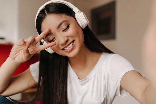 Mulher de cabelo escuro usando fones de ouvido mostra o símbolo da paz e sorri com os olhos fechados