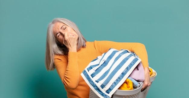 Mulher de cabelo grisalho bonita dona de casa lavando roupa