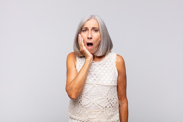 Mulher de cabelo grisalho chocada e surpresa, cara a cara, sem acreditar, com a boca bem aberta