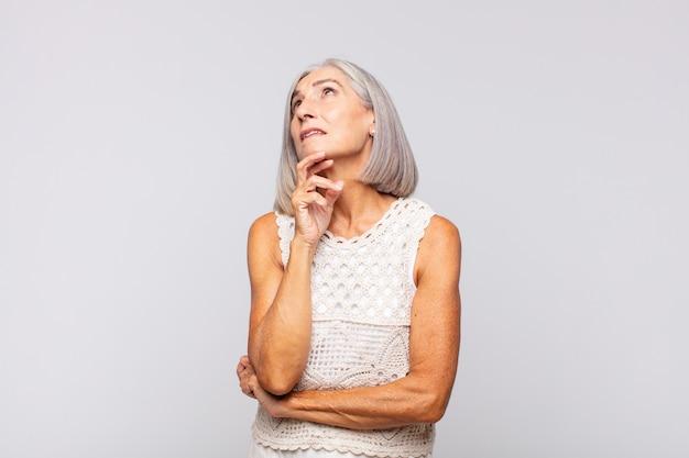 Mulher de cabelo grisalho pensando, pensando ou imaginando ideias, sonhando acordada e olhando para cima para copiar o espaço