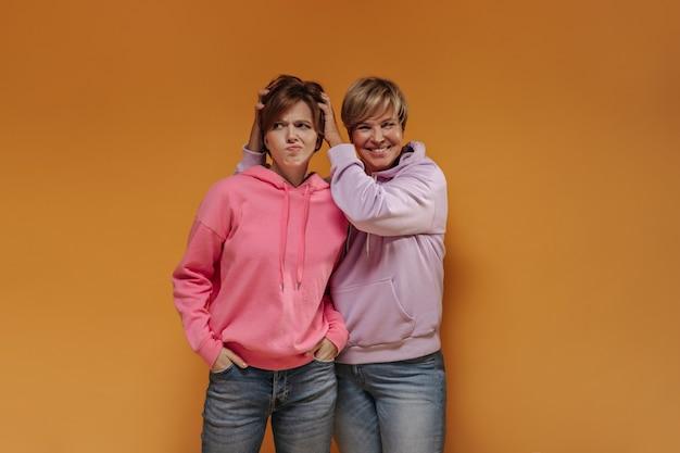 Mulher de cabelo loira alegre com capuz lilás, sorrindo e posando com uma jovem triste em roupas cor de rosa em fundo laranja isolado.