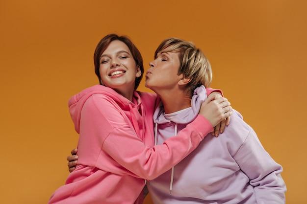 Mulher de cabelo loira com capuz lilás beijando sua neta com cabelo curto escuro em moletom rosa brilhante em fundo laranja.