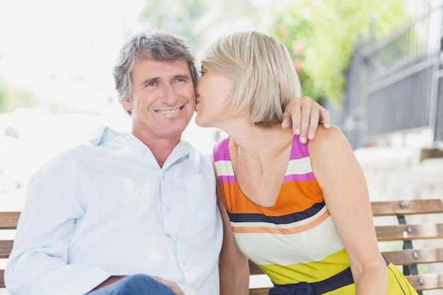 Mulher de cabelo loiro beijando homem no parque