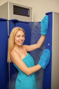 Mulher de cabelo loiro entrar na cabine de sauna de crioterapia