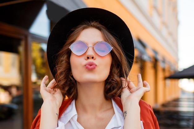 Mulher de cabelo muito curto, mandando beijo do ar. olhar elegante de outono.
