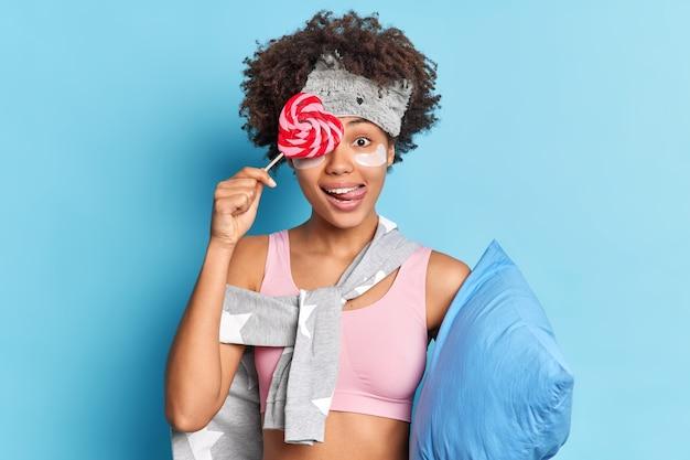 Mulher de cabelo muito encaracolado cobre os olhos com um doce lambe os lábios vestida com roupas casuais aplica adesivos de colágeno antes de dormir segura o travesseiro isolado na parede azul