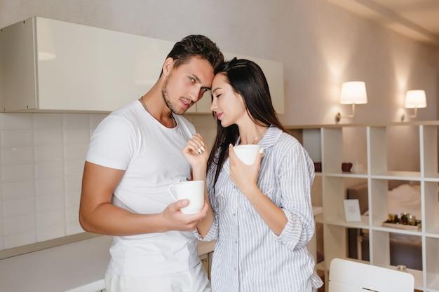 Mulher de cabelo preto com sono na cozinha com o namorado bebendo uma bebida quente