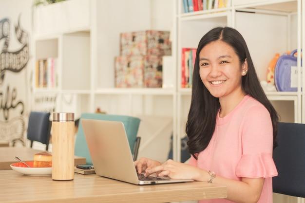 Mulher de cabelo preto sentada em frente ao laptop no escritório