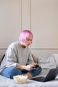 Mulher de cabelo rosa brincando com um joystick no laptop