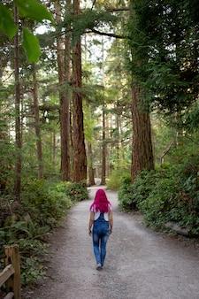 Mulher de cabelo rosa percorrendo um caminho na floresta