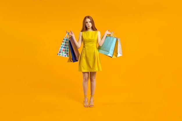 Mulher de cabelo ruivo decepcionada em vestido segurando pacotes de compras chateada por comprar ...