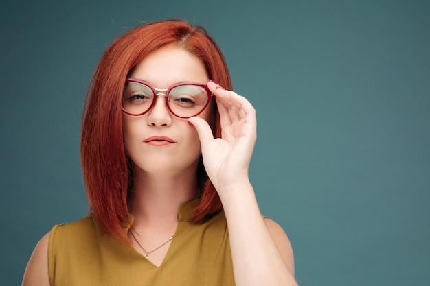 Mulher de cabelo vermelho com maquiagem brilhante e óculos