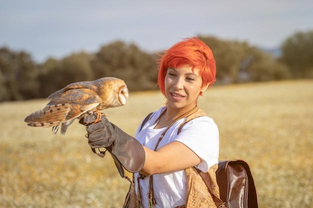 Mulher de cabelo vermelho com uma coruja branca no braço