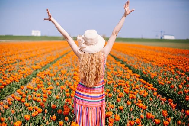 Mulher de cabelo vermelho em pé na parte de trás no campo de tulipa