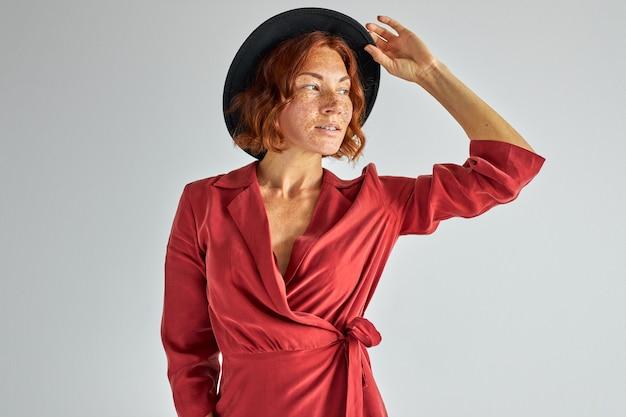 Mulher de cabelo vermelho natural com chapéu olhando para longe em contemplação, posando para a câmera, conceito de pessoas