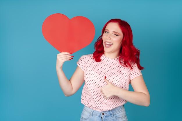 Mulher de cabelo vermelho segurando coração de papel vermelho, pisca, colocando a língua para fora e levanta o polegar