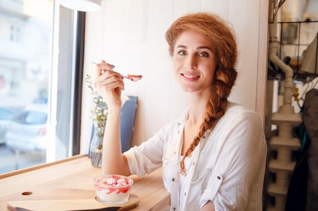 Mulher de cabelo vermelho sorridente, sentado no café e comer sobremesa