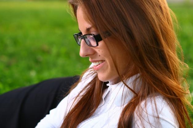 Mulher de cabelo vermelho, trabalhando no parque