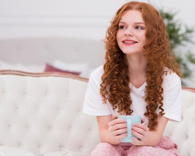 Mulher de cabelo vermelho vista frontal bebendo chá