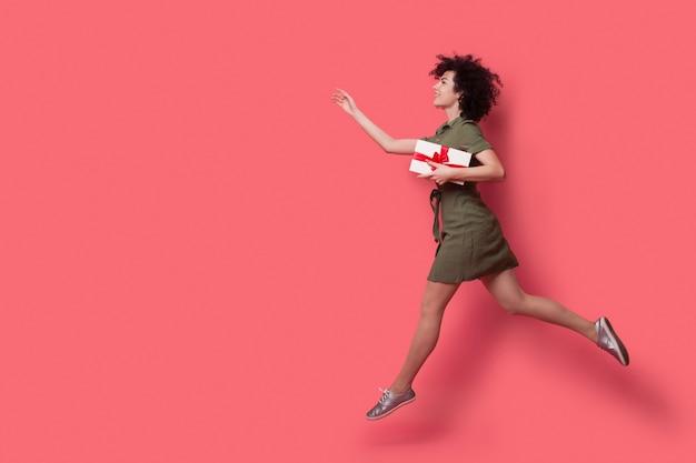 Mulher de cabelos cacheados está correndo e chamando alguém para lhe dar um presente na parede vermelha de um estúdio