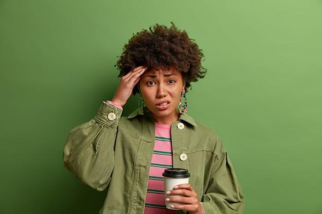Mulher de cabelos cacheados frustrada sofre de dor de cabeça, toca a têmpora, bebe uma bebida refrescante após uma noite sem dormir, segura uma xícara descartável de café, vestida com roupa elegante, isolada na parede verde