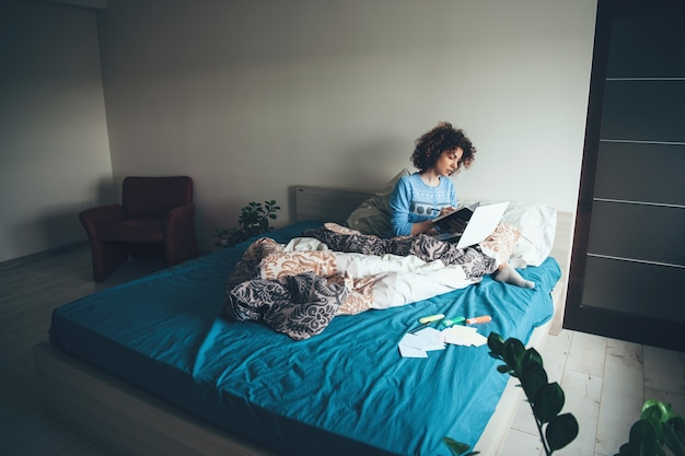Mulher de cabelos cacheados lendo um livro pela manhã, sentada na cama com um laptop
