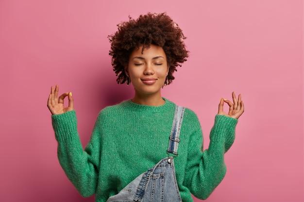 Mulher de cabelos cacheados satisfeita tenta se acalmar, se une à natureza, levanta as mãos e mostra gestos zen, medita ou faz ioga dentro de casa, fecha os olhos, gosta de um ambiente tranquilo para um bom relaxamento