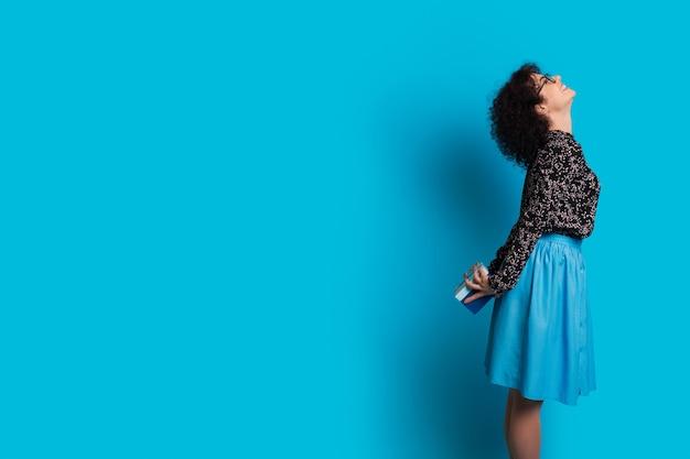Mulher de cabelos cacheados segurando um presente nas costas sorrindo em uma parede azul