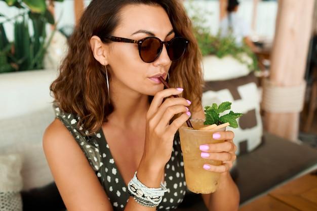 Mulher de cabelos cacheados sorridente em roupa de verão na moda relaxando no café aconchegante, bebendo limonada.