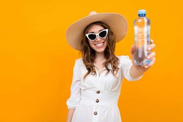 Mulher de cabelos castanho elegante com um sorriso em um fundo amarelo, segurando uma garrafa de água nas mãos, foto com profundidade de campo